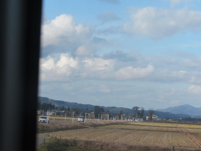 車窓から田んぼが広がる風景を眺める
