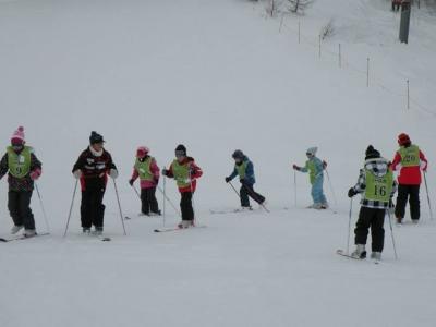 初めてスキーをする子供たちはまず片足ずつスキーを付けて歩いてみます。