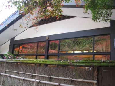 建物の窓に紅葉と鳥居の映り込み
