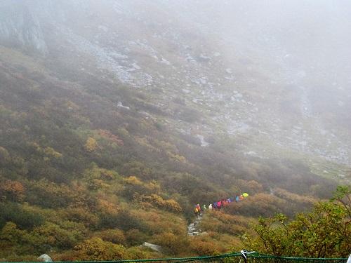 雨・霧の中 カールを進み 登山するグループ