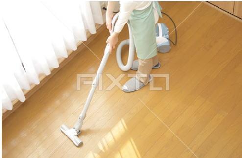 洋室に掃除機をかける女性 ハイアングル2