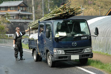 竹が山積みのトラックとまっちゃん