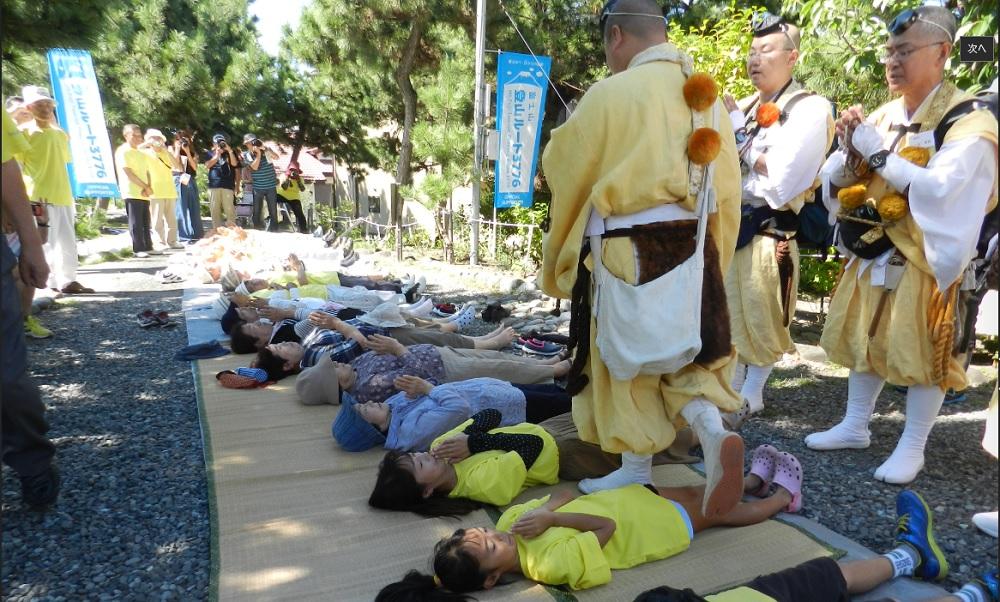 """富士塚で勤行のあと、大人も子供も""""跨ぎ""""を受ける"""