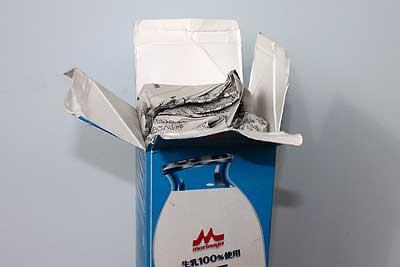 上を切り開いた牛乳パックに新聞を詰める