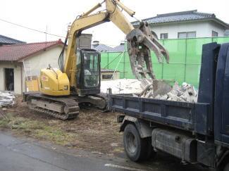 重機で積み込まれる壁の残骸