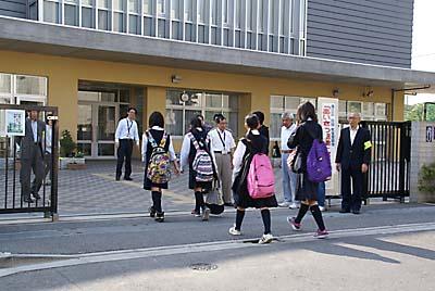 中央中の校門前で地域の人たちとあいさつを交わし合う