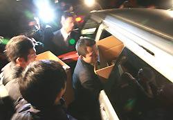 報道陣に囲まれながら押収物を入れた段ボールを車両に運び入れる長崎県警の捜査員