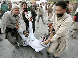 自爆テロのあった現場で負傷者を運ぶ人々=AP