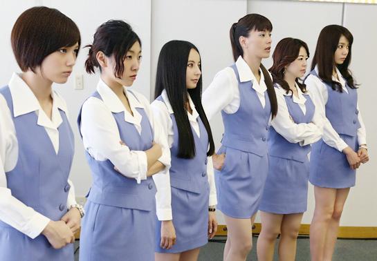 ショムニの制服で腕を組み無表情で相手を見つめる堀内敬子