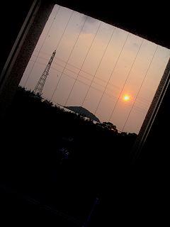 窓越しに見える笠山に沈む夕陽