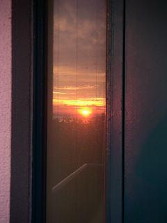 窓に映った夕陽