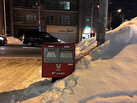 除雪されて道端に積まれた雪、郵便ポストのところだけは雪の壁が切れている