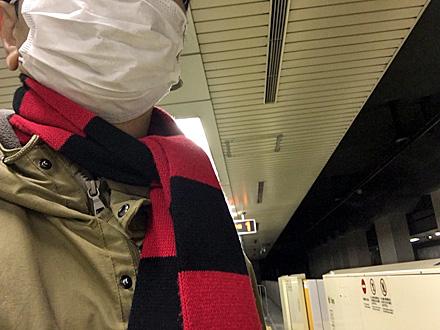 マスク姿で地下鉄の駅のホームに立つ