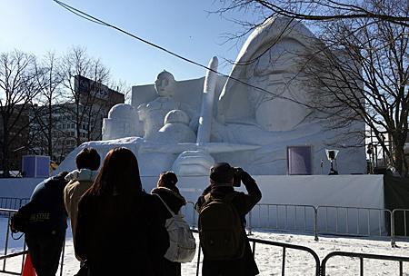 雪像の前に柵があって離れたところから写真を撮っている人々