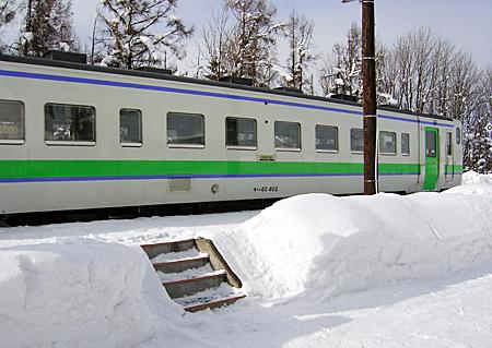 雪のホームに停車中の列車