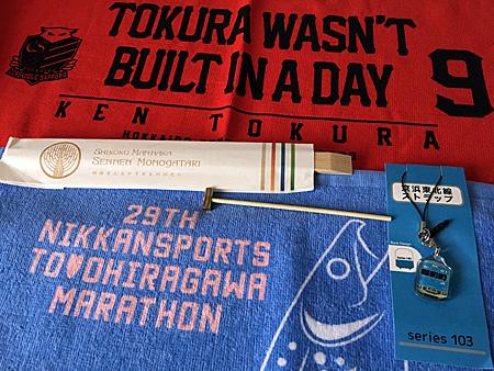 コンサドーレ都倉選手のタオル、豊平川マラソンの参加賞のタオル、京浜東北線電車のストラップ、四国の観光列車の箸袋、べっこう飴を割るためのハンマー