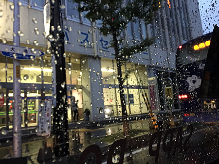 タクシーの窓にたくさんの水滴 向こう側にバスセンター
