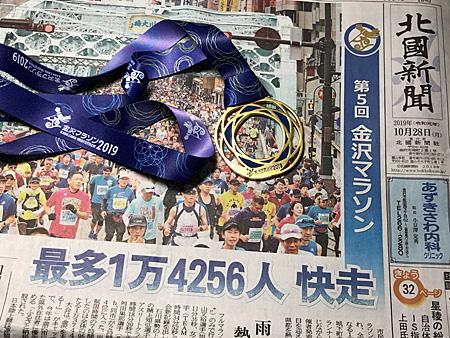 翌日の北國新聞の紙面と完走メダル