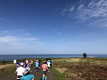 青空の下をオホーツク海に向かって走るランナー