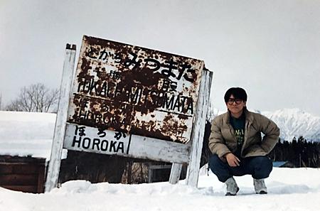 錆びついた駅名標と並んだ記念写真