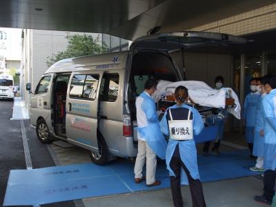 新病院の玄関へ感染症患者様を乗せた搬送車が到着