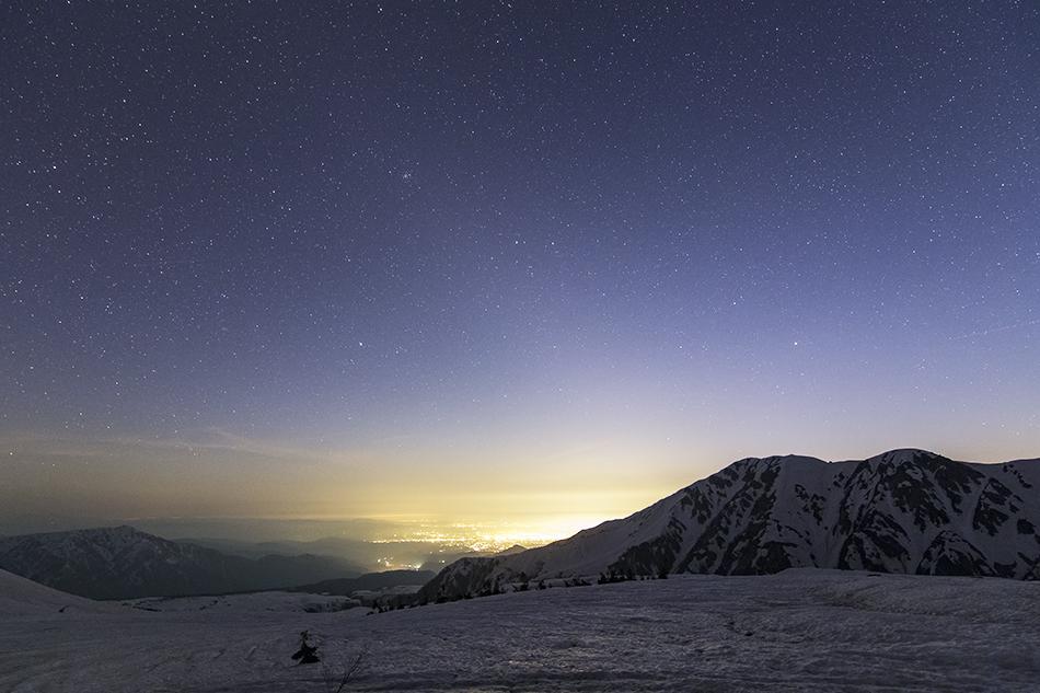 沈む冬の星々と富山市内の夜景