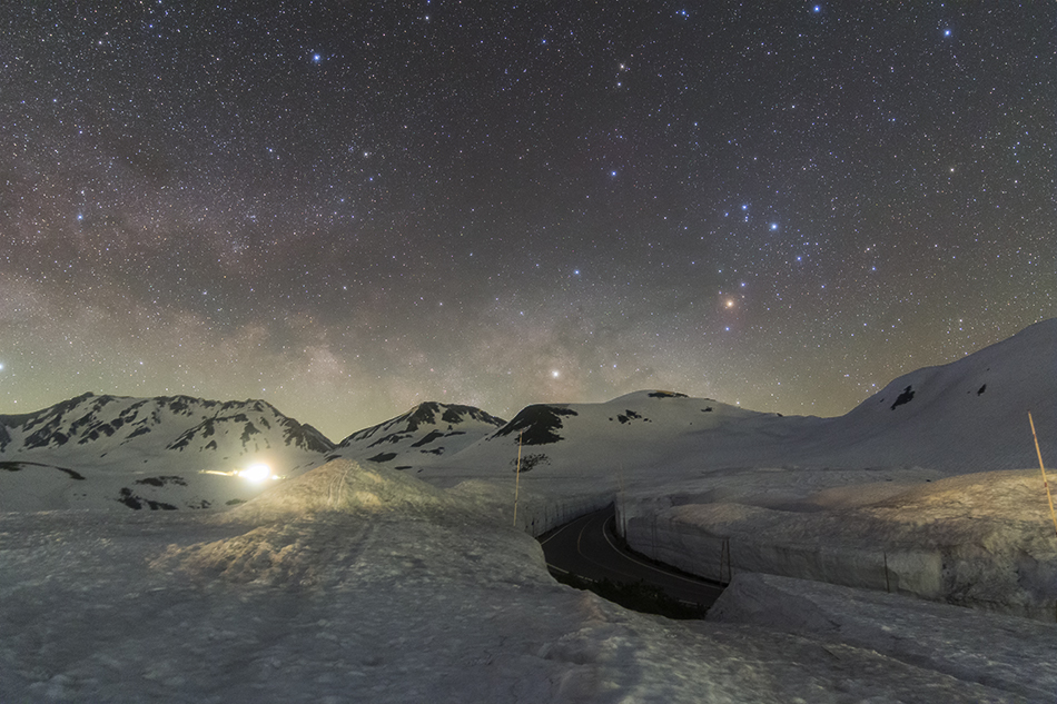 昇るさそり座と雪の壁の道