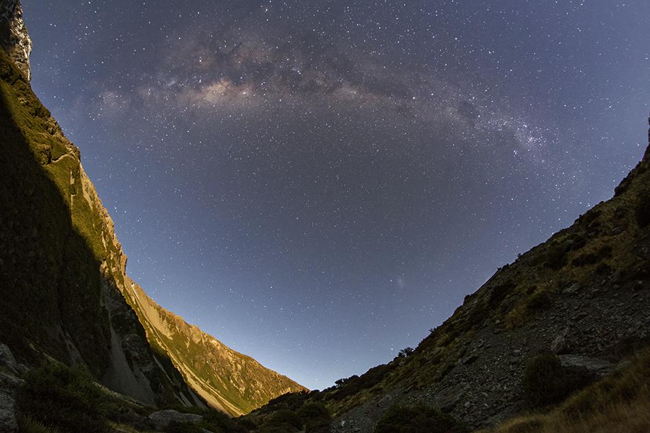 月明かりに照らされた山肌と銀河のアーチ