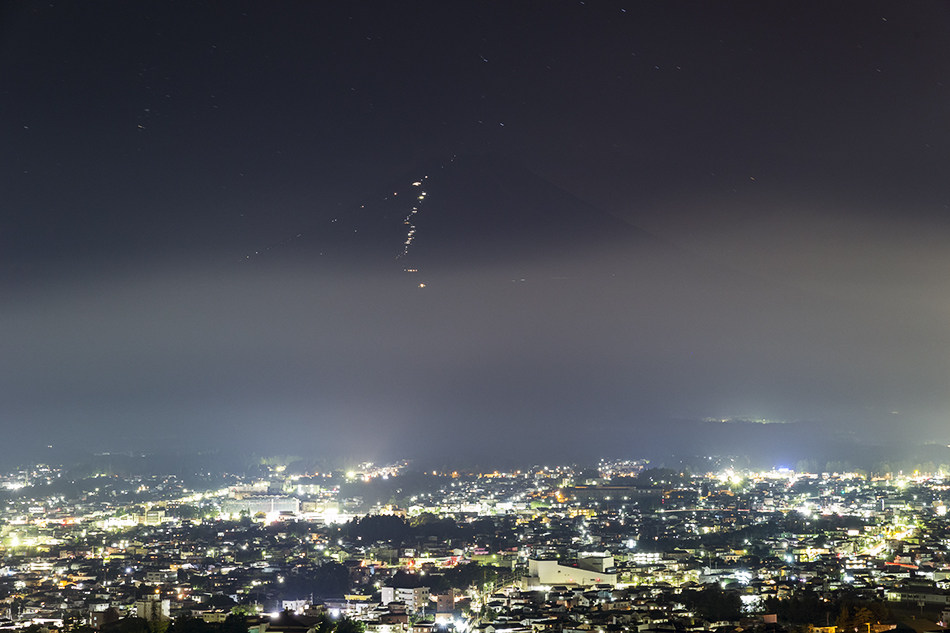 富士山に登る登山者の灯りと街の灯り