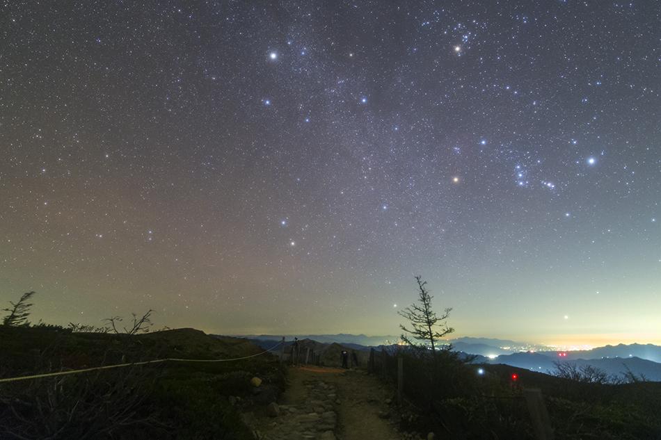 草津白根山昇る冬の星座と夜景