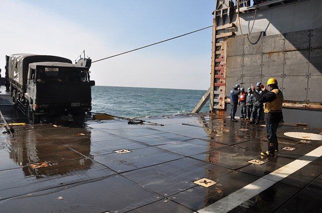 s-800px-US_Navy_110316-N-2348B-012_A_Sailor_aboard_the_amphibious_dock_landing_ship_USS_Tortuga_(LSD_46)_guides_a_Japan_Ground_Self-Defense_Force_truck_car.jpg