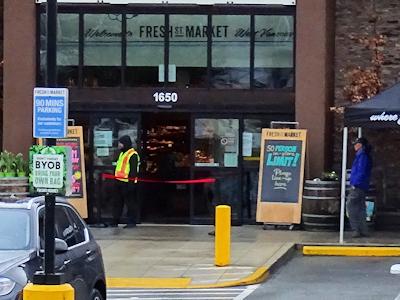 スーパーの入り口で監視するガードマン