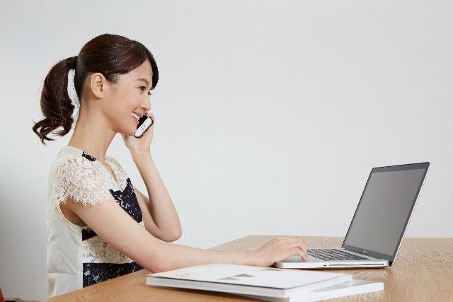 パソコン見ながらスマホで電話する女性